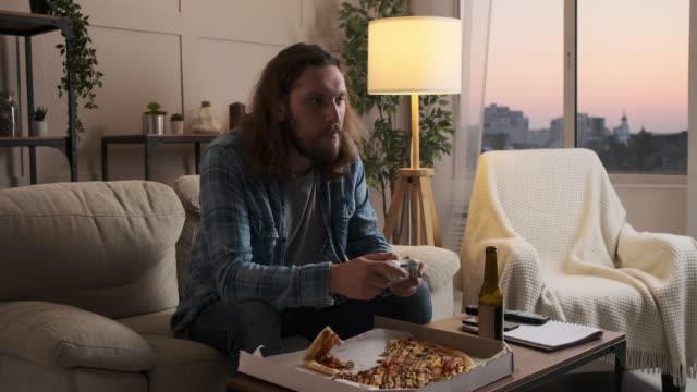 vídeos de stock e filmes b-roll de man enjoying pizza and beer playing video game at home - man joystick