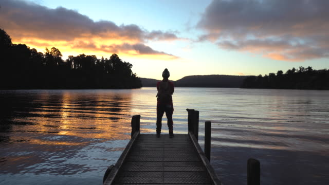 Man enjoying sunset by standing on Jetty. Lake Mapourika is located on the West Coast of New Zealand's South Island. It lies north of Franz Josef Glacier, and the out-flowing Ōkārito River drains it into the Ōkārito Lagoon. It is the largest of the West Coast lakes, a glacier formation from the last ice age. jetty stock videos & royalty-free footage