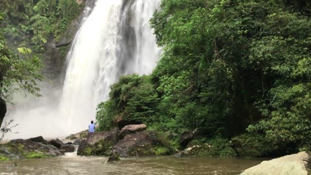 mann (nicht erkennbar), genießen den blick auf einen riesigen wasserfall in einem waldgebiet in brasilien - kaskaden gebirge stock-videos und b-roll-filmmaterial