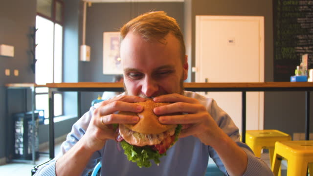 man enjoys eating, tasting the delicious big burger meat - hamburger video stock e b–roll