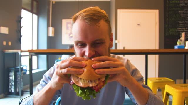 vídeos y material grabado en eventos de stock de hombre goza comiendo, degustación de la carne deliciosa hamburguesa grande - hamburguesa