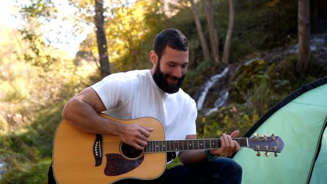 en man tycker om att spela gitarr på camping - akustisk gitarr bildbanksvideor och videomaterial från bakom kulisserna