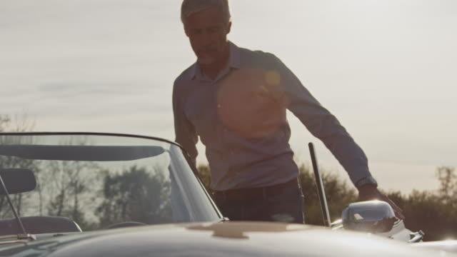 man entering classic car for road trip - вход стоковые видео и кадры b-roll