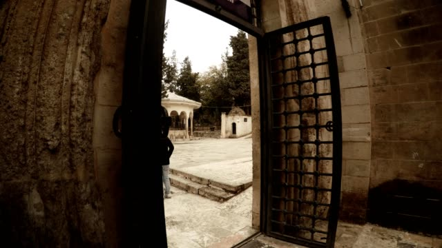 Man Enters in Gate with Lattice Doors in Yard of Old Mosque Urfa video