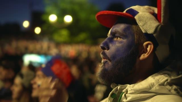 vídeos de stock e filmes b-roll de man european football team coughs off flu soccer stadium night background crowd - soccer supporter portrait