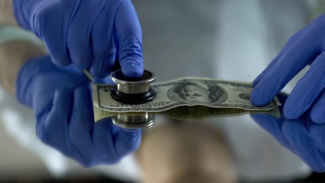 mann, untersuchungsrichter dollar mit stethoskop, symptome der wechselkurs fallen - inflation stock-videos und b-roll-filmmaterial