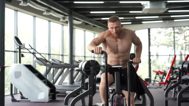 남자 운동 자전거 체육관 사이클링 훈련 피트니스. 에어 바이크 카디오 운동을 사용하여 피트니스 남성. - 한 명의 중년 남자만 스톡 비디오 및 b-롤 화면