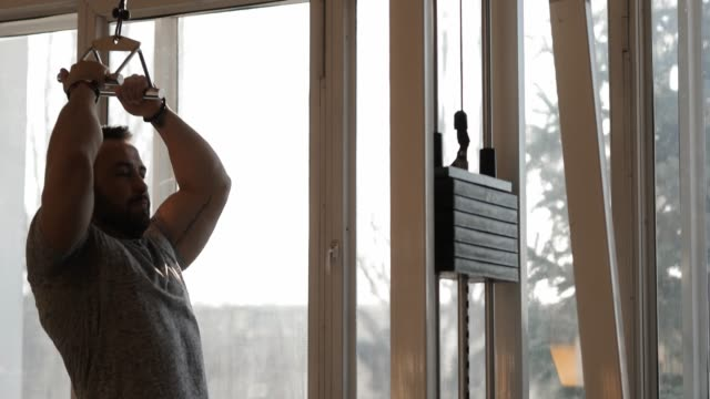 ジムで運動する男性は、ラティシムス・ドルシの筋肉をより強くする - 人の筋肉点の映像素材/bロール