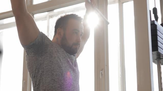 ジムで運動する男性は、筋肉をより強くする - 人の筋肉点の映像素材/bロール