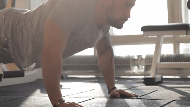 Man exercising in a gym making push-ups Man exercising in a gym making push-ups on a floor and clap hands bodyweight training stock videos & royalty-free footage