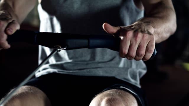 vídeos de stock, filmes e b-roll de homem, exercitando-se na máquina de remo no ginásio - remo atividade física