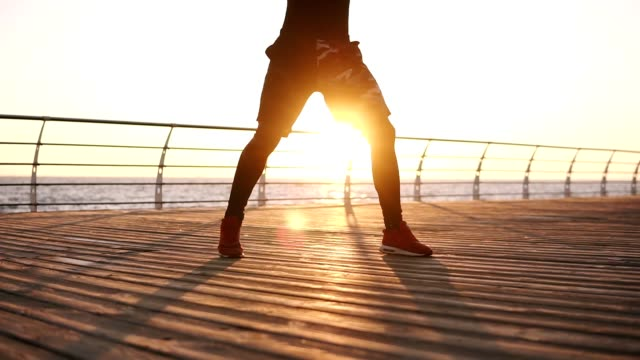 Man Exercising on Seaside Promenade Boxer standing in front the the sunrise above the sea on the wooden floor doing exercises legs. Endurance training for a boxer, you only see the feet. doing the splits stock videos & royalty-free footage