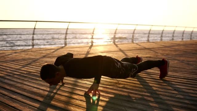 man exercising on seaside promenade - tułów filmów i materiałów b-roll