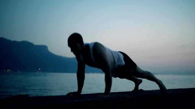 Man exercising push ups silhouette Man exercising push ups in dusk. push ups stock videos & royalty-free footage