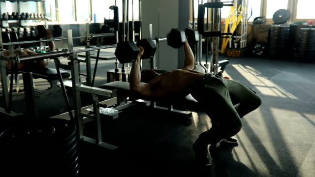 stockvideo's en b-roll-footage met man trainen met halters in sportschool - bankdruktoestel