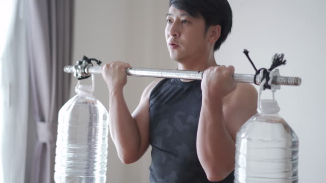 Man exercising with homemade dumbbell/barbell from plastic water gallon indoors