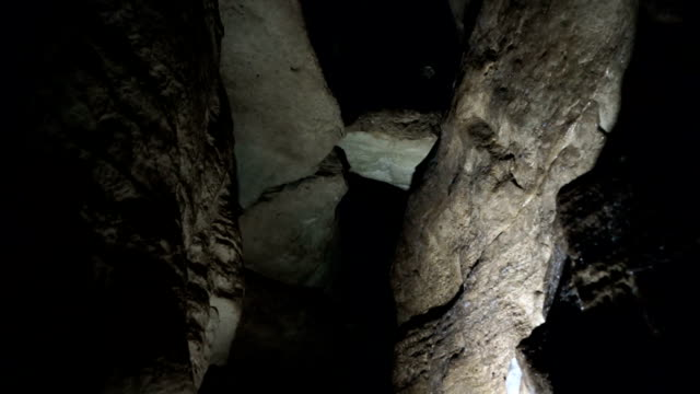 Man explores cave with light in narrow cave video