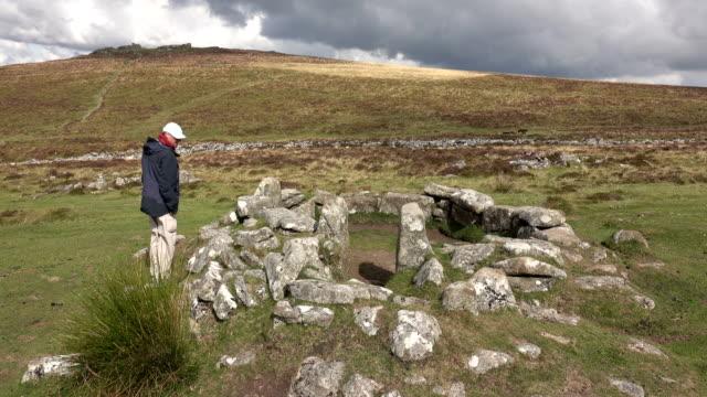 man utforskar förhistoriska cirkulär byn grimspound dartmoor national park devon england storbritannien - fornhistorisk tid bildbanksvideor och videomaterial från bakom kulisserna