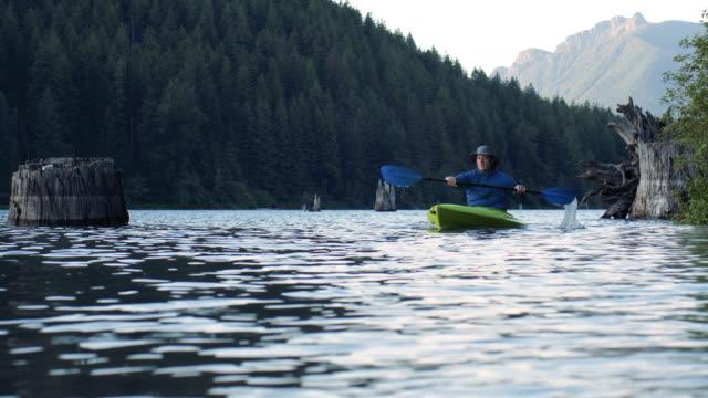 アルパイン湖を探索する男パドリングカヤックスローモーション ビデオ
