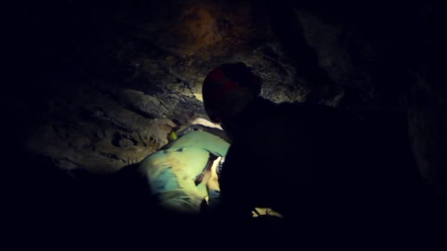 man exploring dark cave with flashlight - кейвинг стоковые видео и кадры b-roll