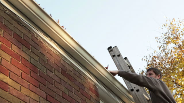 stockvideo's en b-roll-footage met man falling off ladder while cleaning gutters - slow motion - achteloos