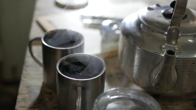男は紅茶でステンレス カップで眠っている砂糖に落ちる - マグカップ点の映像素材/bロール