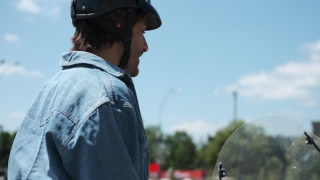 vídeos de stock e filmes b-roll de man fastening helmet strap on scooter in city - helmet motorbike