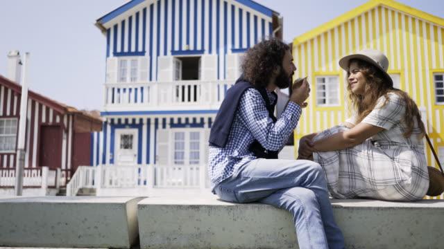 vídeos de stock e filmes b-roll de man feeding girlfriend near colorful buildings - aveiro