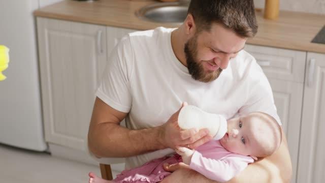 человек кормления новорожденного с формулой в бутылке - кормить стоковые видео и кадры b-roll