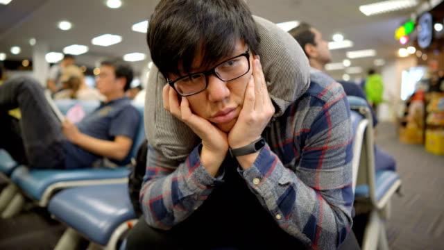 vídeos y material grabado en eventos de stock de hombre sintiéndose aburrido por esperar retraso de vuelo en el aeropuerto - esperar