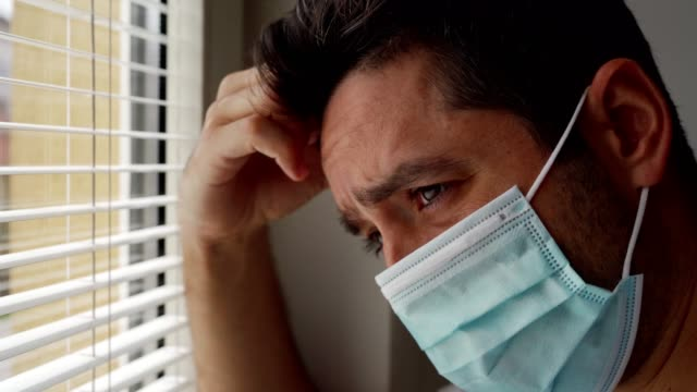 Man feeling lonely during coronavirus epidemic Close-up video of young man looking sadly through the window because of the social distancing during coronavirus epidemic. anxiety stock videos & royalty-free footage