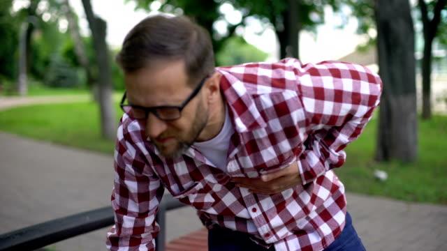 vídeos de stock e filmes b-roll de man feeling sudden chest pain, sitting on bench in park, cardiology, health - ataque cardíaco