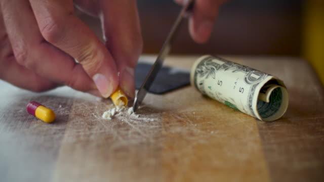 man fyller en kapsel med förfalskade droger med hjälp av en metallkniv - amfetamin pills bildbanksvideor och videomaterial från bakom kulisserna