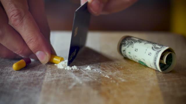 man fyller en tom kapsel ett vitt pulver som betyder falska droger - amfetamin pills bildbanksvideor och videomaterial från bakom kulisserna