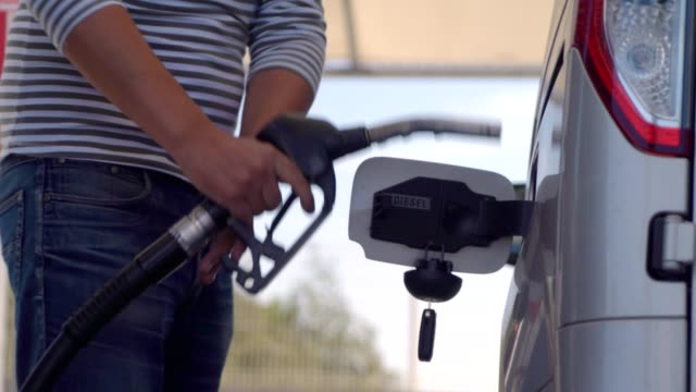 Man filling car with Diesel Fuel. Fuel nozzle inserted in car diesel tank and refueling Man filling car with Diesel Fuel. Fuel nozzle inserted in car diesel tank and refueling the fuel tank of the car refueling stock videos & royalty-free footage
