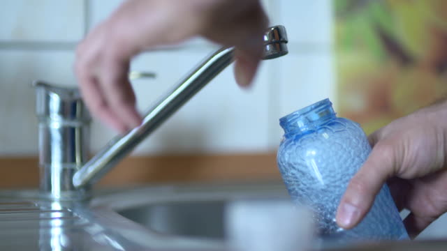 Man Filling Water In Bottle From Faucet Over Sink video