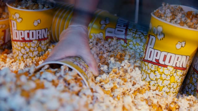 man fills bucket with popcorn in fast food cafe close view
