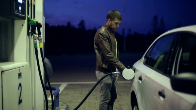 Man fills his car with gasoline at night video