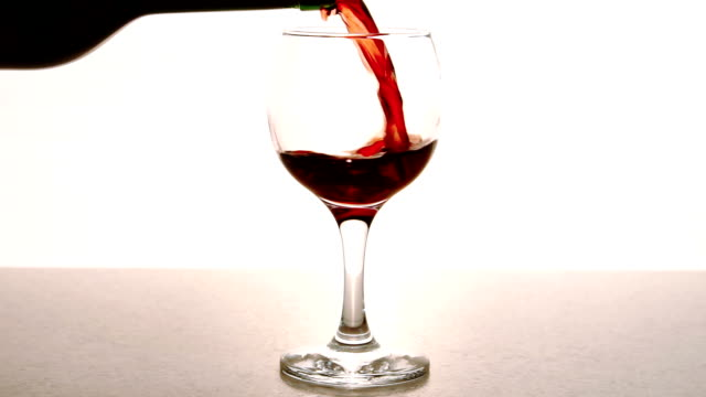 Man fills transparent glass with red wine in restaurant indoor video