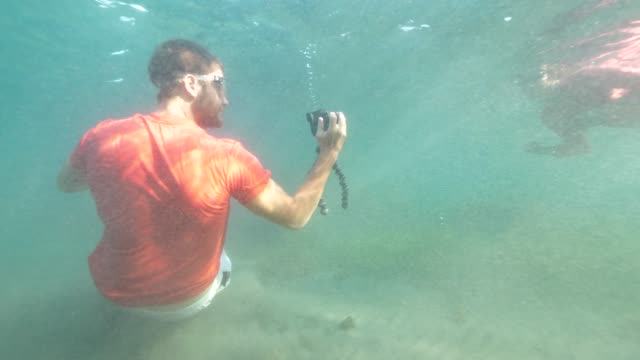 A man filming a snorkeling woman underwater using a digital camera.