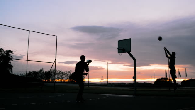 MS Man filming basketball players shooting hoops on outdoor basketball court at dusk