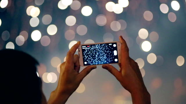 Man filming colorful fireworks on his cell phone video
