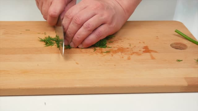 a man finely cuts dill with a japanese knife santoku, hands, close-up - articoli casalinghi video stock e b–roll