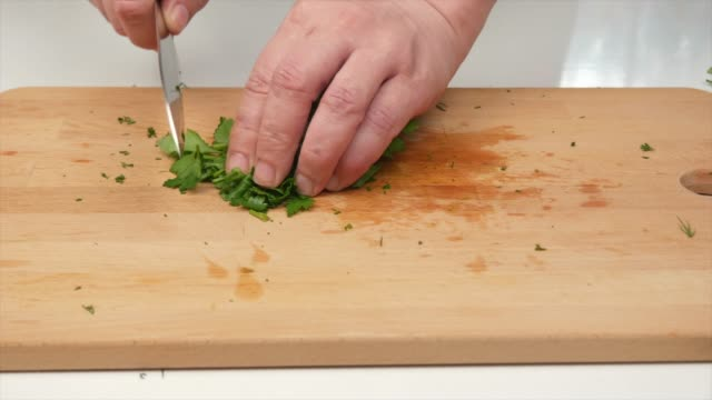a man finely cuts parsley with a japanese knife santoku, hands, close-up - articoli casalinghi video stock e b–roll
