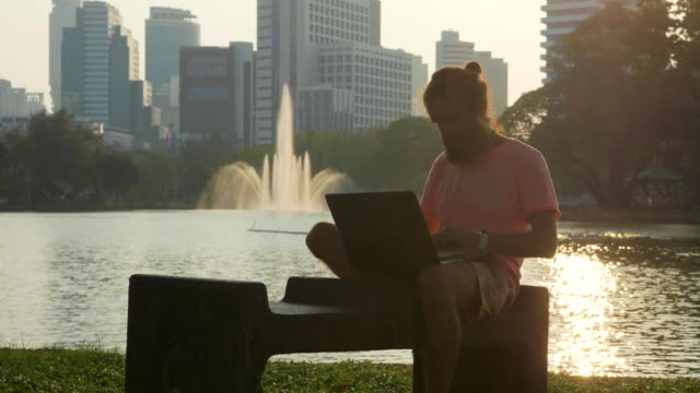 man finish the work and closed laptop while he sitting on the bench at city park - bench stock videos & royalty-free footage