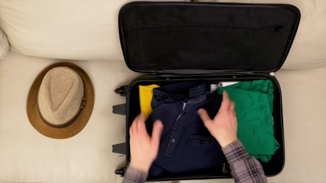 Man finishing packing clothes into a travel bag video