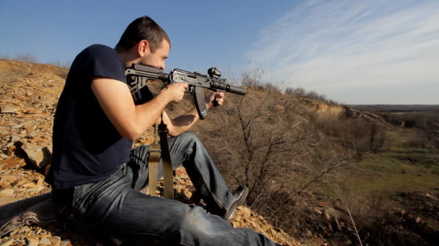 man firing customised russian machine gun, wide video