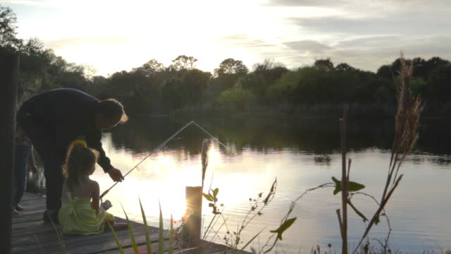 Hombre de la pesca en puesta de sol - vídeo