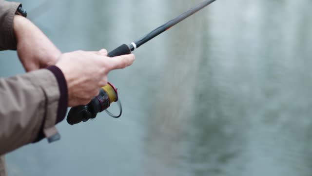 男釣り。釣り竿を手に持っている漁師。 - 釣りをする点の映像素材/bロール