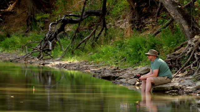 Man Fishing From River Bank HD video